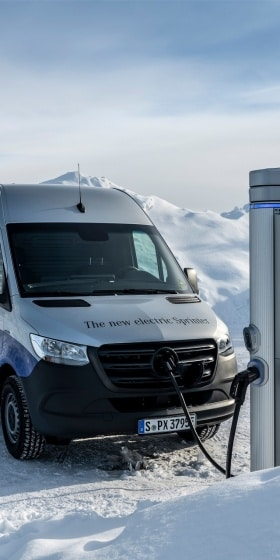 A Mercedes-Benz eSprinter at a charging station in a snowy landscape