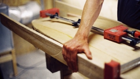 A hand fixes a wooden surfboard to a workbench