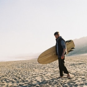 Stefan runs along the beach with his surfboard under his arm