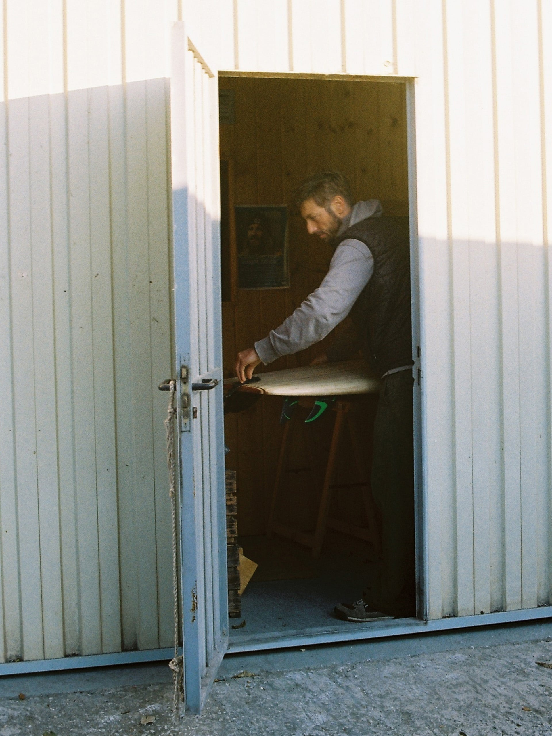Stefan working on a surfboard, viewed through the open door of his workshop
