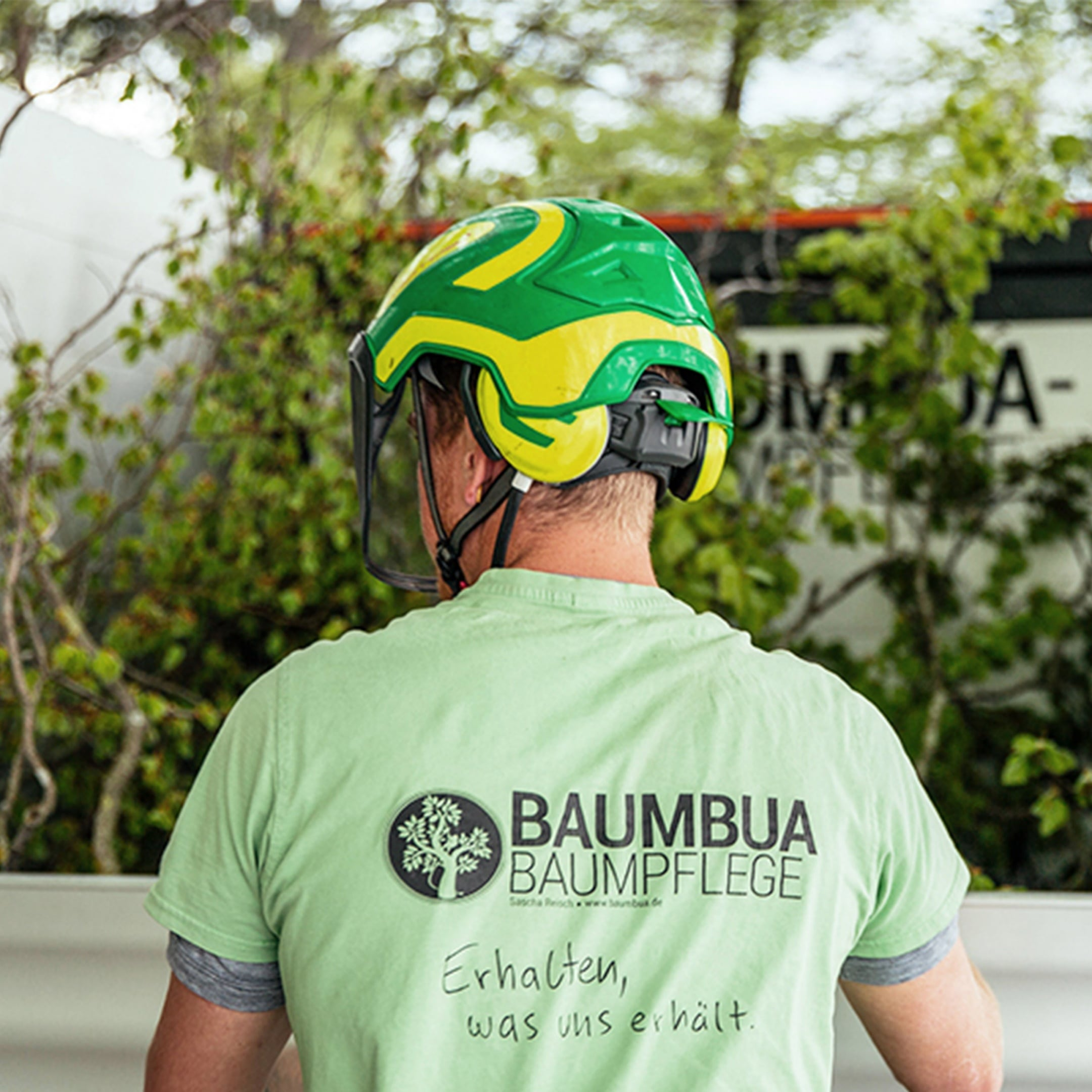 A man wearing a helmet and a T-shirt with the Baumbua logo printed on the back