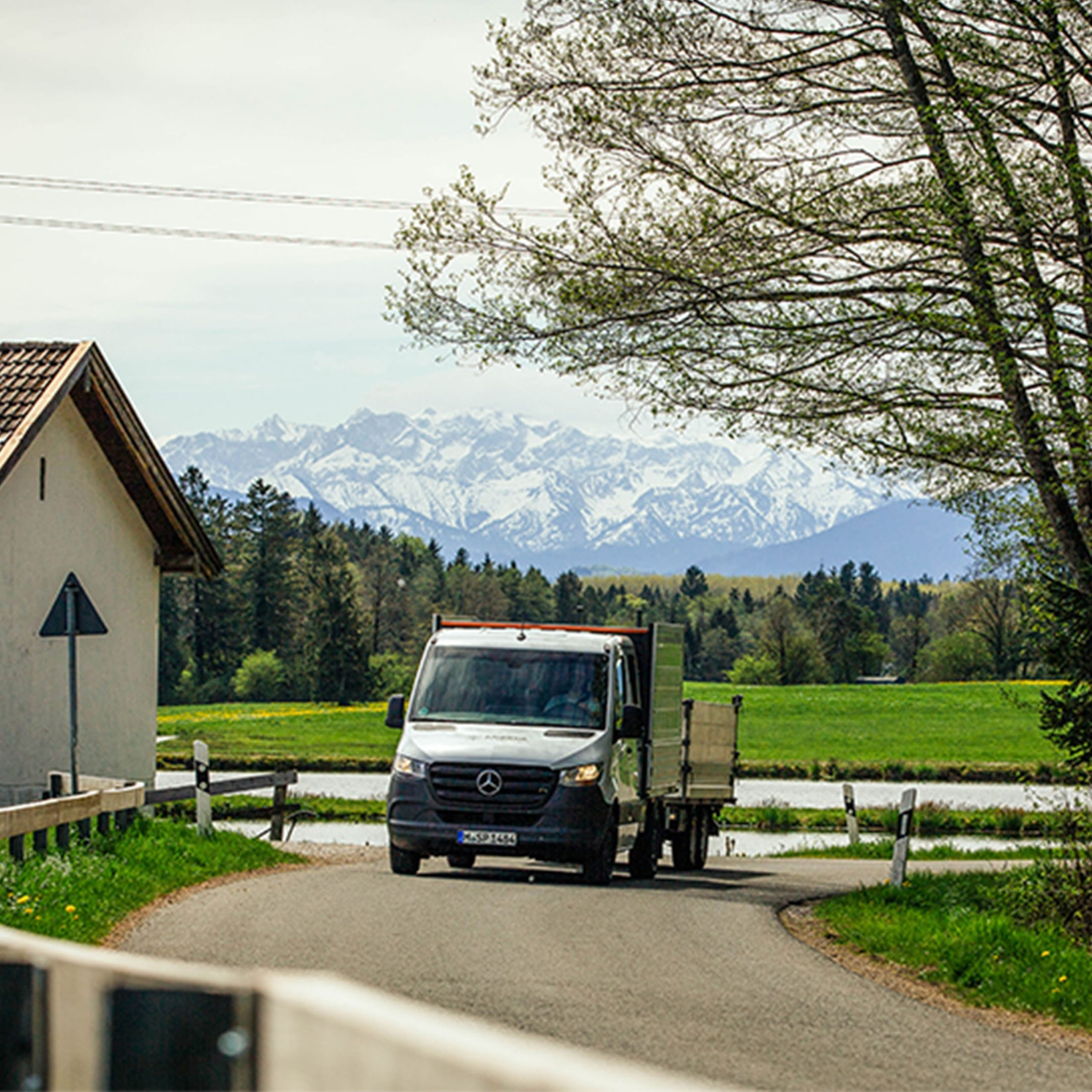 A Mercedes-Benz Sprinter drives along a winding road