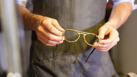 The glasses maker holds the almost-complete glasses in his hands