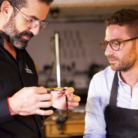 The optician and the master craftsman of the glasses frame both take a look at the finished glasses