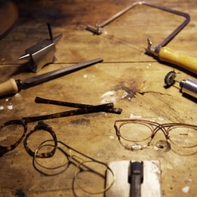 The individual components of a pair of glasses are set out on a workbench