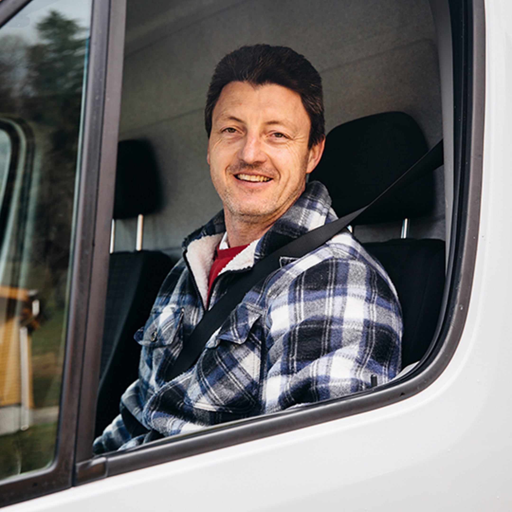 A man sitting behind the wheel of a Sprinter looking through the side window into the camera
