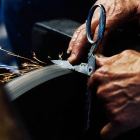 Two hands grind the blade of a pair of scissors