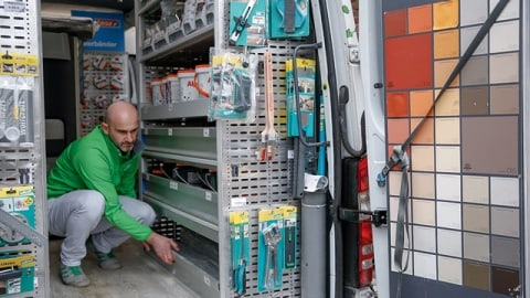 A man crouches down in a fully-equipped Sprinter and opens a cupboard