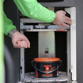 A pot of paint in a machine being operated by two hands