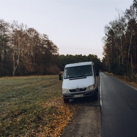 """Emil"" the Sprinter is parked on the side of the road near a forest"