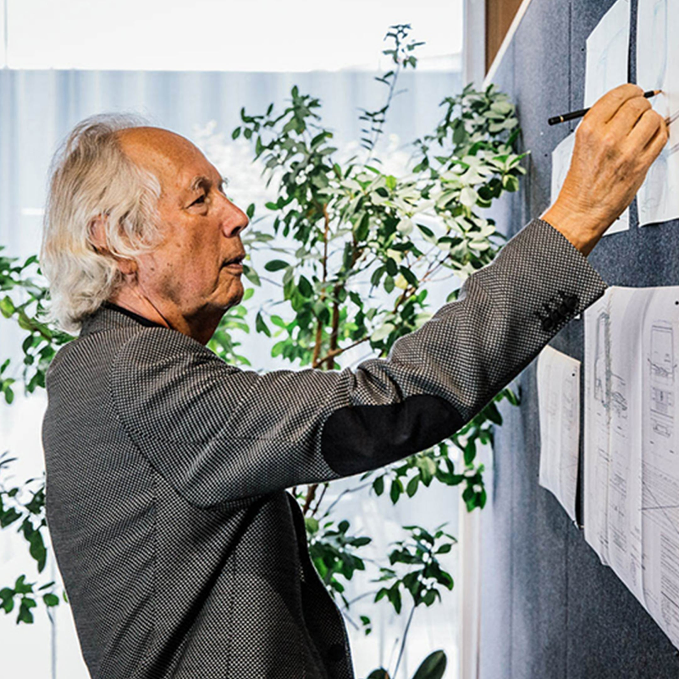 A man standing in front of a pin-board and drawing