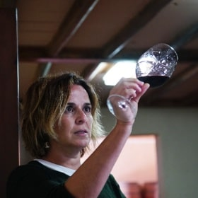 A woman looking at wine in a glass
