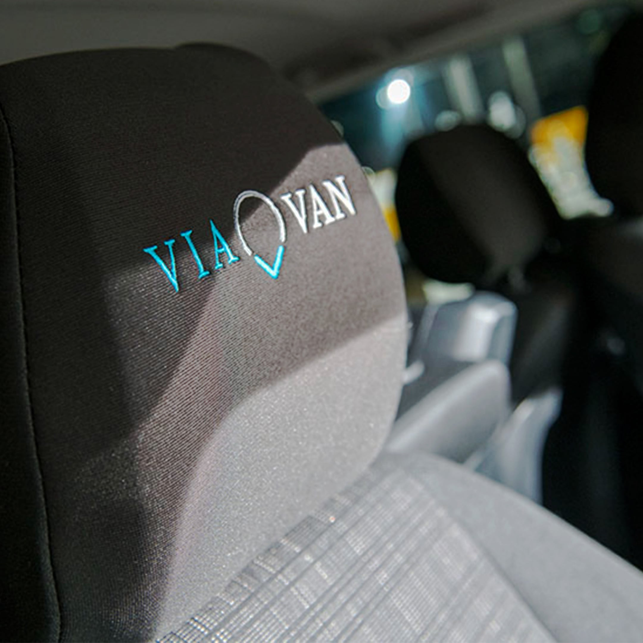 A car seat head restraint embroidered with the ViaVan logo