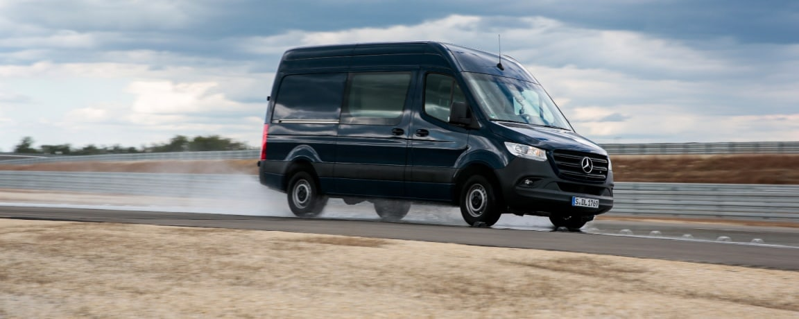 A Mercedes-Benz Sprinter driving on a wet road