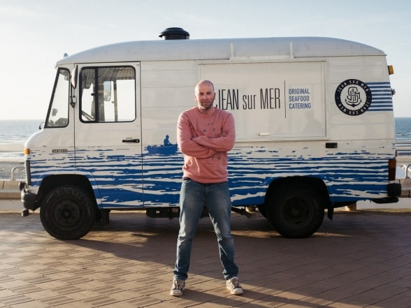 A man is standing in front of a Mercedes-Benz 508 D food truck