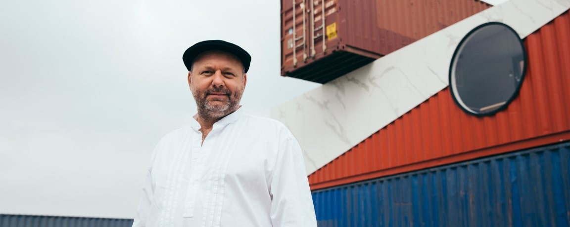 Ivan Mallinowski standing in front of three stacked containers. One of them is a living container