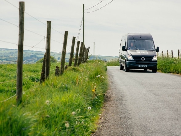 A Mercedes-Benz Sprinter driving along a road out of town