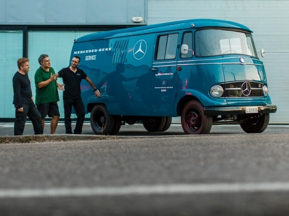Three men are walking next to a Mercedes-Benz L 319
