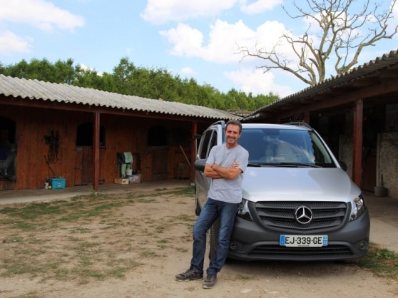 Wolfgang Albert standing in front of his Vito with horseboxes in the background