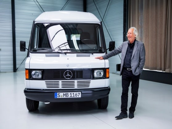 A man standing next to a white Mercedes-Benz T 1 in a hall