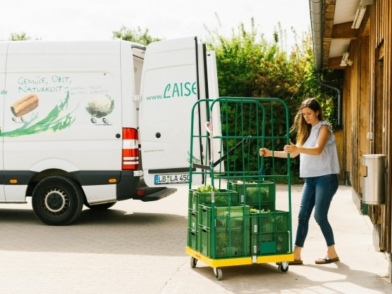 Tabea Sanzio pushes a trolley full of vegetable crates