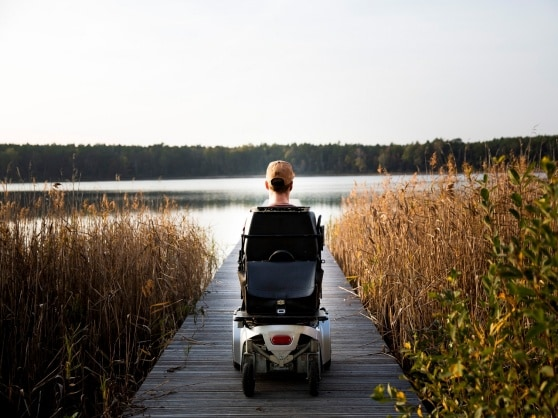 A disabled man sitting in a wheelchair and looking out across the lake