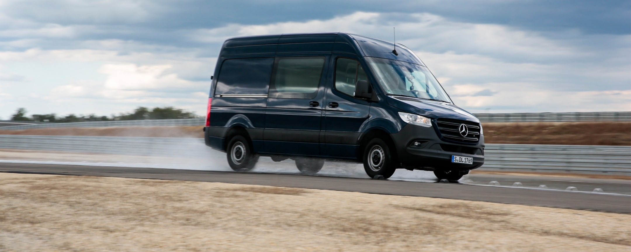 A Mercedes-Benz Sprinter is driving on a wet road