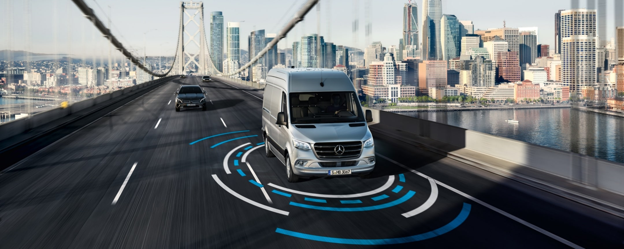 A Mercedes-Benz Sprinter with active safety systems driving along a bridge