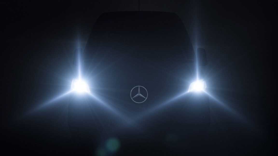 A Mercedes-Benz Sprinter in the dark, with bright headlamps