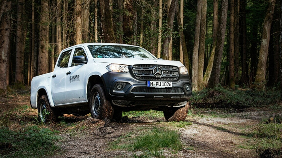 An X-Class driving through a forest