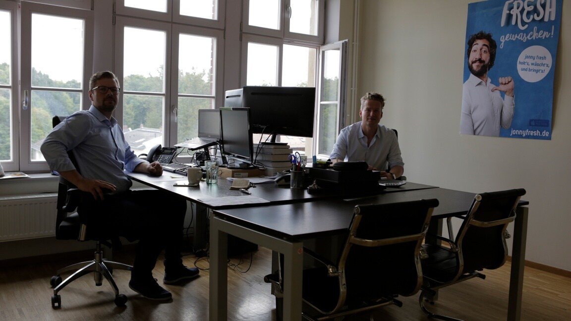 Two men sitting in an office at their desks opposite one other and looking into the camera