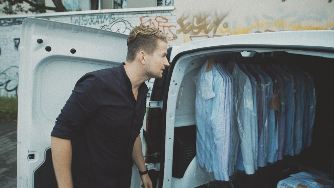 Stefan opens the load compartment of the Citan where shirts are hanging on clothes rails