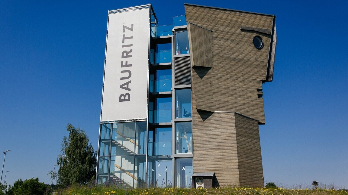 A modern building in the shape of a head adorned with the Baufritz lettering