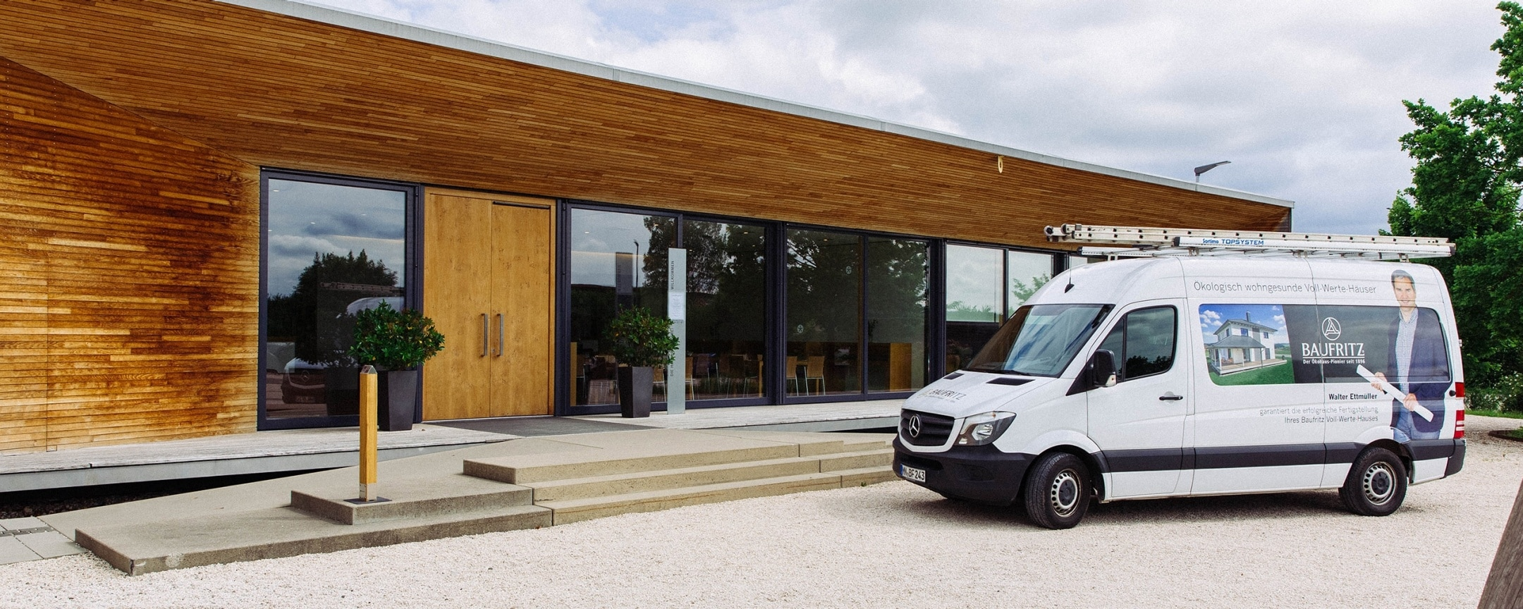 A white Mercedes-Benz Sprinter is parked in front of a house with a wooden façade