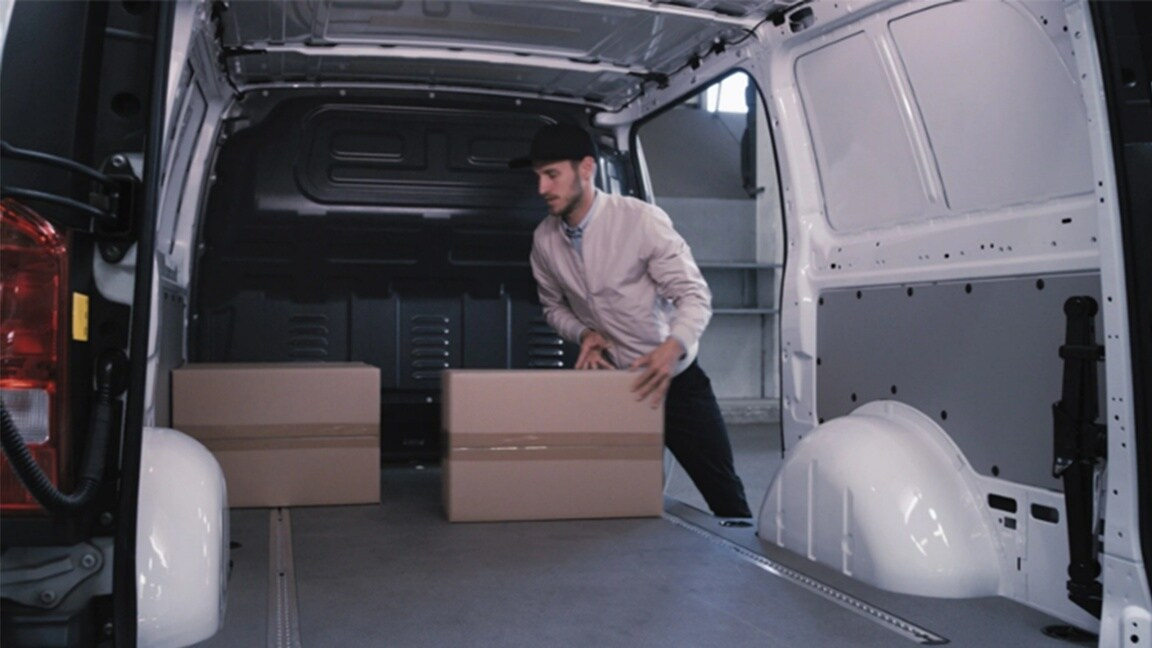 Parcels are placed in the load compartment of a Mercedes-Benz eVito